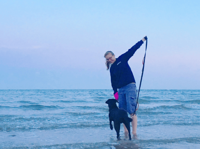 a woman and a dog paddling in the sea
