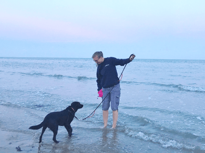 a women teaching her dog about the sea